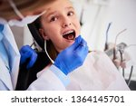 Small photo of Part of orthodontist examining child's teeth in dentist's office