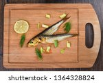 Stock photo two baltic herrings cold smoked with dill green onions and lime on a wooden cutting board two 1364328824