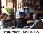 Stock photo waitress female welcoming diverse cafeteria pub guests african guy mixed race girl making order 1364480027