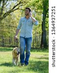 man with dog on the phone in... | Shutterstock . vector #1364937251