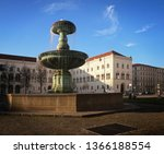 Fountain at Professor Huber square in Munich, Germany with the buildings of the Ludwig Maximilian University