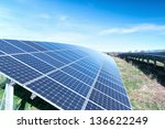Field with many solar cells in front of a blue sky - stock photo
