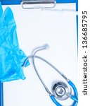 on the clipboard are: stethoscope, syringe and gloves - stock photo