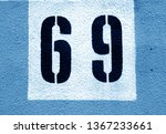 Number 69 on cement wall in stencil in navy blue tone. Abstract background and texture for design.