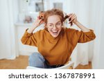 Small photo of Cute mischievous young redhead woman pulling her pigtails while winking and sticking out her tongue with a teasing expression