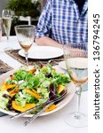 Healthy green vegetable salad served on a table set for a party outdoors in the garden - stock photo