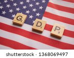Small photo of Maski,India 13,April 2019 : Finance Concept, GDP or Gross domestic product wooden block letters on US Dollar flag