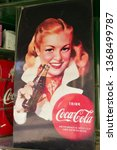 Small photo of Montevideo Uruguay 14 April 2019. Old coca cola advertisement hanging outside the walls of a kiosk in the square of independence.red hair woman smiling holding coke bottle. Red budge of coca cola