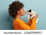 Stock photo profile shot of pleased dark skinned female kisses small french bulldog expresses love to 1368598907