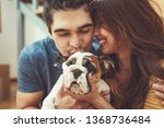 Stock photo the young happy couple is moving into a new house they are hugging their little puppy after 1368736484
