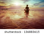Stock photo yoga and fitness silhouette of woman meditating on the beach 136883615