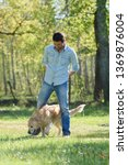 man having fun with his dog... | Shutterstock . vector #1369876004