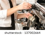 Barista steaming milk for hot cappuccino with machine - stock photo