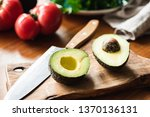 halved avocado on wooden... | Shutterstock . vector #1370136131