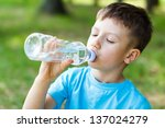 little boy drink water  outdoor | Shutterstock . vector #137024279