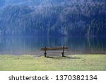 wooden bench at a mountain lake ... | Shutterstock . vector #1370382134