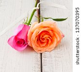 Two beautiful orange and pink roses on tight together on rustic wood table. - stock photo