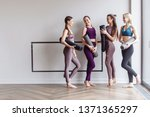 Small photo of Four beautiful slim positive young girls fitness models are preparing for joint training and rejoice at the meeting. The concept of sports lifestyle and like-minded people. Yoga concept