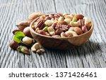 nuts in wooden plate in closeup | Shutterstock . vector #1371426461