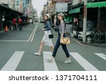 Small photo of two happy female friends travelers with bags crossing street together outdoor sunny day in china town. japanese lady travel in chinese city walking on zebra cross in urban. girl wear hats look at sky.
