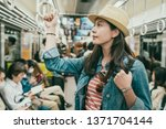 Small photo of young female asian traveler hand holding handle standing on subway train. elegant lady with straw hat commute by public transport in japan osaka. people in metro doing self thing quiet sitting seat