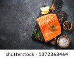 Stock photo fresh salmon fish uncooked salmon fillet with ingredients for cooking on black stone table top 1372368464