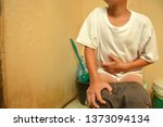 asian boy aches stomach while... | Shutterstock . vector #1373094134