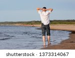 Young Man Walking On The Beach...