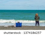Man Fishing On The Beach With...