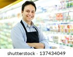 Storekeeper smiling in his grocery store  - stock photo
