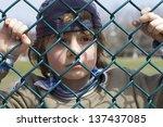 Sad Little Boy Behind A Fence