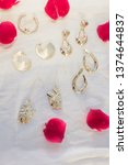 gold earrings on linen fabric... | Shutterstock . vector #1374644837