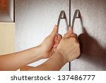 Stock photo women s hands closed the cupboard doors dark wood 137486777