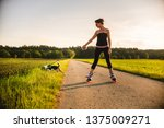 Stock photo girl skating with dog outdoors in nature on a road to forest sunny day countryside sunset 1375009271