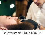 Small photo of Cutting mustache with sharp scissors. Barber in black hygienic gloves concentrate in scrupulous work process. Mustache styling and cutting. Advertising for barber shop. Side view. Blurred background.