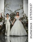 Small photo of NEW YORK, NY - APRIL 11: Designer Madeline Gardner and model walk the runway during the Morilee by Madeline Gardner Spring 2020 fashion show at New York Fashion Week: Bridal on April 11, 2019 in NYC.