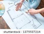 Young husband and wife moving to new place sitting on floor looking at apartment project plan close-up