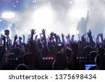 Stock photo concert silhouettes of happy people raising up hands music show bright scene lighting in club 1375698434