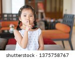 Small photo of Asian child cute or kid girl squat and forefinger close mouth for tell quietly shh or stop silence and secret surprise with play hide and seek in library room at school or reception room