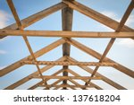 Construction of roof, wooden pine symmetric skeleton and blue sky. - stock photo