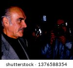 Small photo of LOS ANGELES - circa 1991: Sean Connery walks by paparazzi as he departs Spago restaurant in this unaltered image