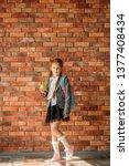 schoolgirl with schoolbag holds ... | Shutterstock . vector #1377408434