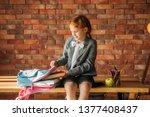 cute schoolgirl puts textbook... | Shutterstock . vector #1377408437