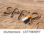 Small photo of Sun protect factor. SPF word written on the sand and white bottle with suntan cream with question mark. Skin care concept background.