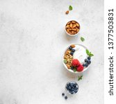 Small photo of Granola with yogurt and berries for healthy breakfast. Bowl of greek yogurt with granola, almonds, blueberries and strawberries, top view, copy space.