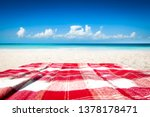 Red And White Blanket On Sand...