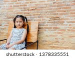 Stock photo little girl sitting on a chair with brown brick background 1378335551