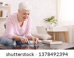 Stock photo activity can improve brain function elderly woman sitting at table and sorting jigsaw puzzle 1378492394
