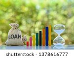 Small photo of Term loan, financial concept : Loan bag, rising bar graph, hourglass on a table, depict loan from bank for specific amount, has specified repayment schedule with either fixed or floating interest rate