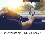 Small photo of Driver using GPS navigation in mobile phone while driving car at sunset